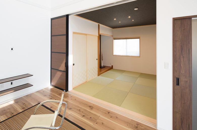 普段はリビングの続きとして広々使える和室は、来客時にはスクリーンパーテーションで仕切れます。 天井をダークにすることで、落ち着きのある空間に仕上がっています。