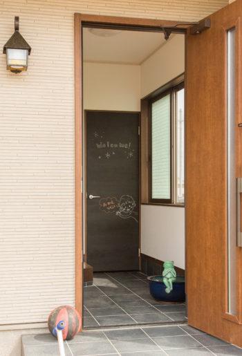 玄関に黒板塗料を施した建具をあしらって。奥様のイラストとWELCOMEの文字が優しく迎えてくれる。