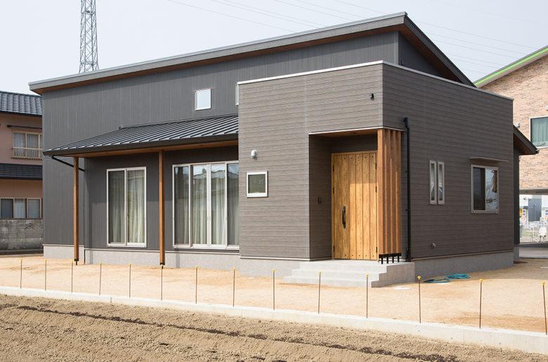 ダイナミックな片流れ屋根。木目調のサイディングに柱がアクセントになって雰囲気を和らげています。