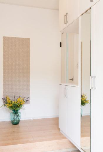 お客様を迎える明るい玄関には大収納のシューズボックスと、正面にはエコカラットを張って。