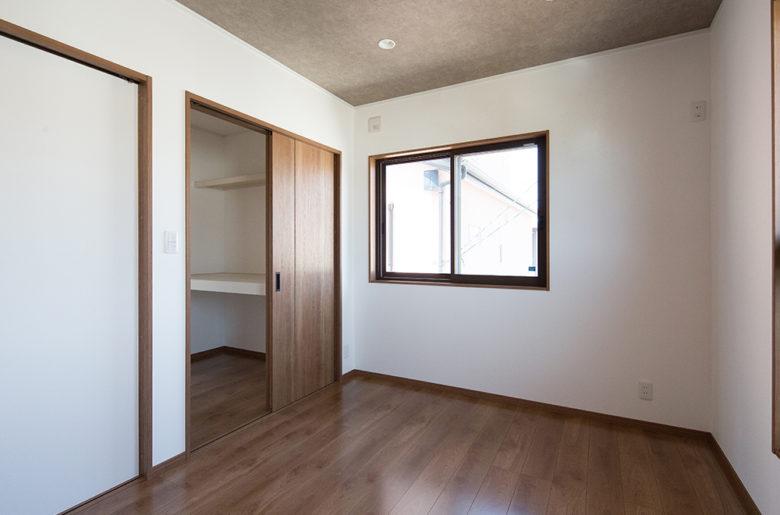 寝室はちょっとシックな色合いで。天井はグレーの石目柄をセレクト。高さがおさえられて落ち着きをもたらす。