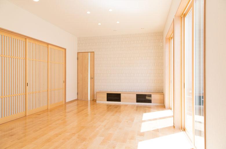 天井高2m70cmで広々とした明るいリビング。巾広の無垢フロアが印象的。隣接した和室との間に設けられた化粧格子の建具が一層の上質間を添える。