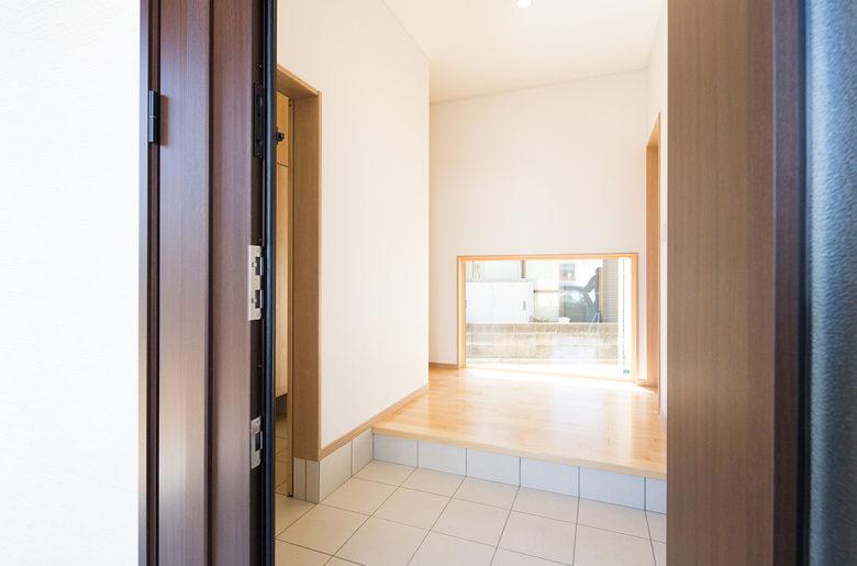 玄関ドアをあけた正面に設けた地窓。玄関が明るく、抜け感もあり心地よい。一層広がりを感じる。