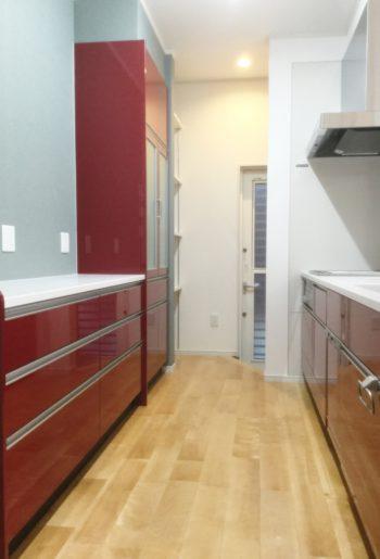 スタイリッシュな赤のキッチン。奥には可動棚のパントリー。サイズの異なる様々なものが収納出来て便利です。