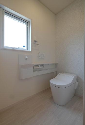 タンクレスで広々。白とベージュのワントーンで仕上げたナチュラルで爽やかなお手洗い。