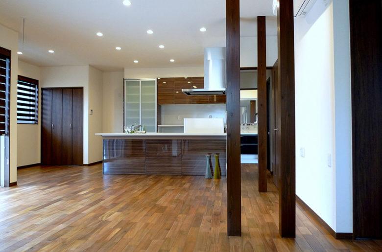 """重厚感のあるウォールナットの床材を敷き詰め、広く大きな空間に、アクセントとして化粧柱を3本並べたLDK。 時を重ねるごとに素材感が際立つ""""樹""""は、住まう人にやすらぎと癒しを届けます。"""