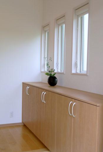 シューズボックスをあえて下段のみに抑え、上部に窓を取ることで、光と風を取り込む事に成功した玄関。