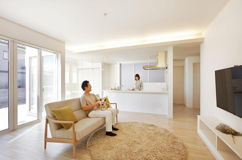 なるべく家を広く見せるため、色は白を基調に、LDKは天井を高く。 下がり天井からの間接照明がやわらかく照らします。 キッチンのすぐ横にダイニングスペースがあり、動線もコンパクト。