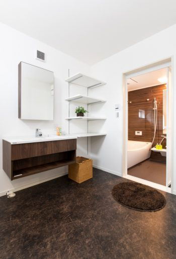 広い洗面室はご主人のお気に入り。床の色を浴室と合わせてダークブラウンで統一。 フロートタイプの洗面台が映える空間。