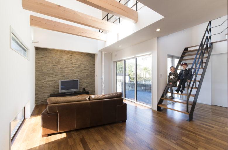テレビ台の壁面は、照明の陰影が美しく出るように凹凸のある素材を選択。 リビング階段はアイアン手摺で軽やかに。