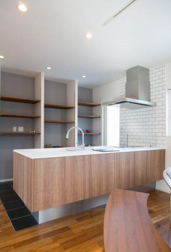 ウッド調のキッチンまわりの床と壁はタイル貼りで空間に変化。 背面収納は扉をつけず見せる収納に!