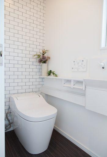 トイレは清潔感のある白とタイル調のクロスでコーディネート。