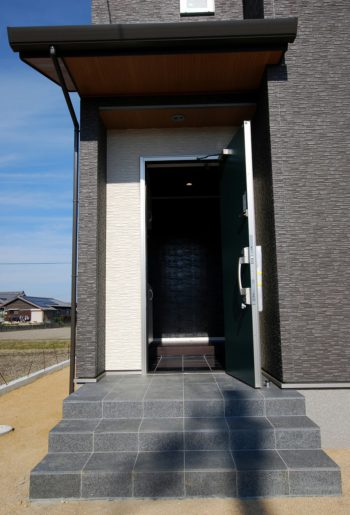 玄関ポーチに高級感あふれる御影石をあしらって。壁面のクロスと相まってきらめくブラックが美しい。