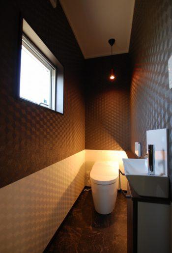 まるで店舗のトイレのような設え。こちらもモノトーンでまとめ、間接照明でのライティング。
