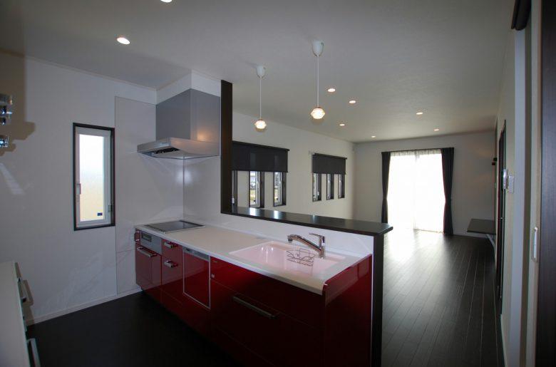 キッチンにはすっきりとした赤をチョイス。モノトーンの空間によく映える。