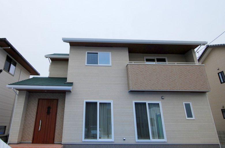 木目調×レンガ調の外壁に白い窓枠、落ち着いたグリーンの屋根で柔らかい印象に。