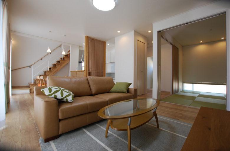 20帖の広々リビングは白×茶でナチュラルモダンな印象に。白壁にスケルトン階段、縁なし畳を使用し、スッキリとまとまりのある空間が実現。