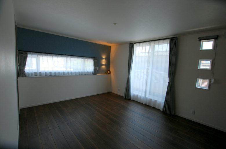 寝室はウォールナットの床で落ち着いた部屋に。窓下の造作カウンターはベッドを置くとちょうどいいサイズ。小物のディスプレイや目覚まし時計の指定席としても活用。