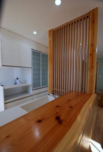 一枚杉のカウンターと縦格子が印象的なキッチン。リビング側からの目隠しにもなっており、ソフトに空間を仕切っている。