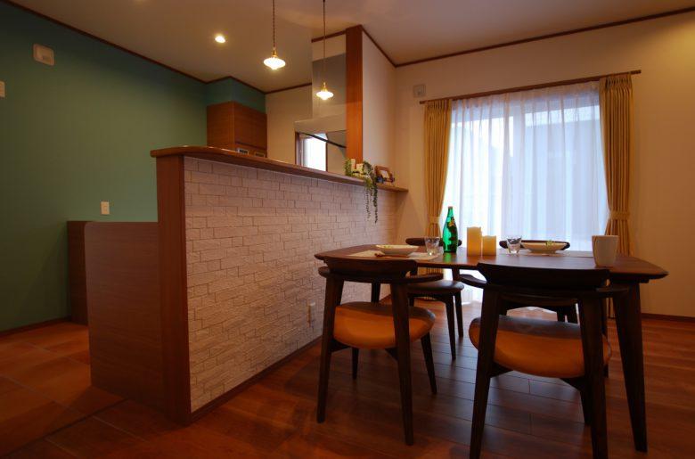 キッチンカウンターの背面を有効活用し、調湿・消臭機能に優れたエコカラットを施工。 夜にはランプシェードの優しい光が部屋に温かみを添える。