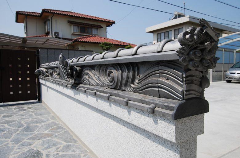 アプローチに既築の棟瓦を再利用。流水紋に鯉や龍の彫刻が施された名品。また新たに歴史が刻まれる。