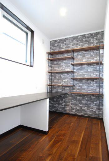 ご主人の書斎。高さを変えられるウォールナットの可動棚がアクセント。カウンターはブラックで引き締めて。