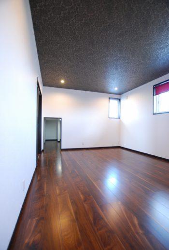 寝室の天井にはシックなデザインクロスをセレクト。奥の小さな入り口をくぐると小屋裏を利用した収納庫が!空間を最大限に活用。