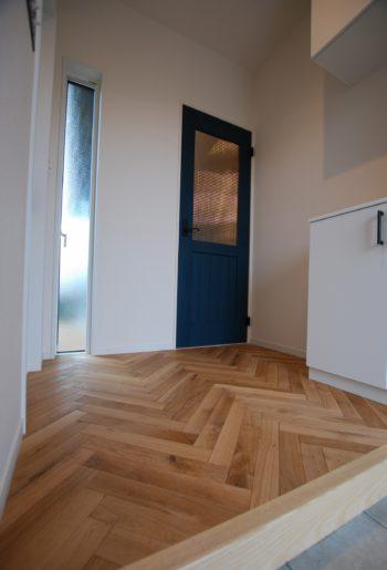 玄関ホールを無垢のヘリンボーン貼でこだわりを魅せる。カラーペイントドアとの相性も◎!