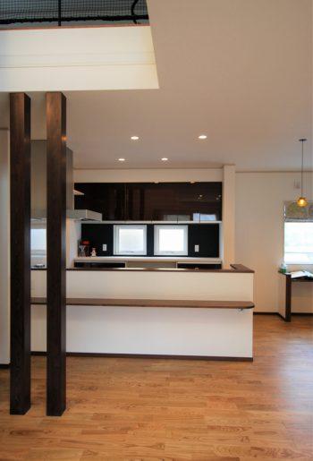 オープンタイプのキッチンを臨んで。奥に見える深いグリーンはこの家のキーカラー。吊戸の鏡面扉とのコントラストも美しい。