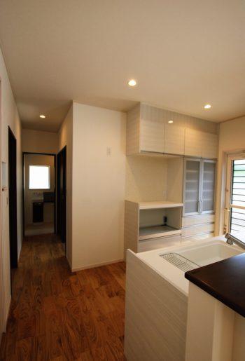 リビングとの一体感を持たせた対面キッチン。 無垢フロアの床色とホワイトカラーのキッチンの対比が、より一層上品さを際立たせる。