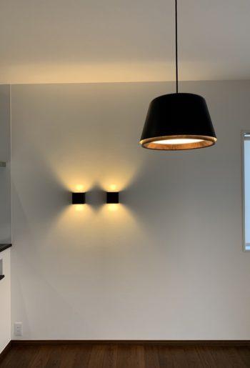 木の質感が心地良く、柔らかい光のランプ。壁のブラケットとともに、明かりの重心を下げることで、空間にくつろぎをもたらしている。