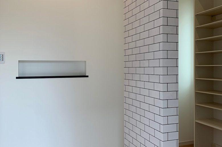 家族用と来客用で仕切りを加えた明るい玄関。 タイル風のクロスが特別感を演出。