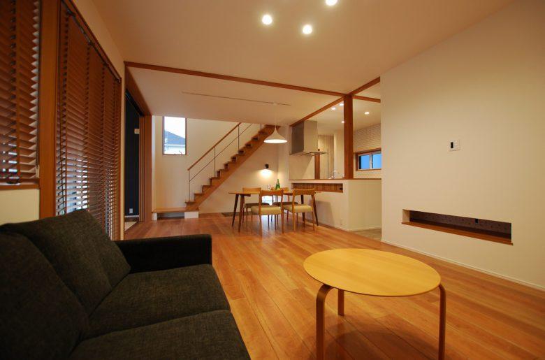 リビングソファよりLDK を眺めて。 開放的な階段がより奥行きのある空間をつくる。 キッチンの化粧柱を軸に伸びる化粧梁が空間のアクセント。
