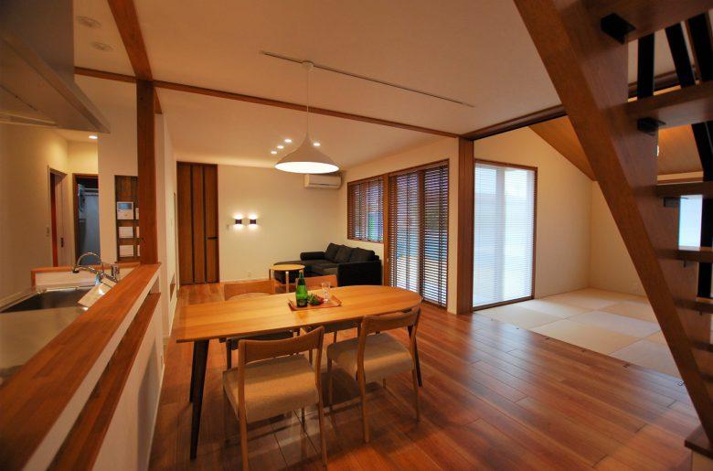 リビングドアの横にはあえて少し低い位置での間接照明。 全体の木質感に併せて、掃出窓に木製ブラインドをあしらって空間をまとめる。