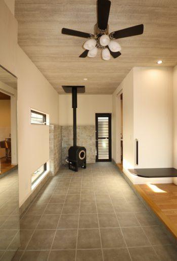 玄関を入ると、開放感たっぷりの広々とした土間。 来訪したお客様と気どらずにコミュニケーションがとれる場になりそう。 寒い季節には暖炉が部屋中を暖めてくれる。