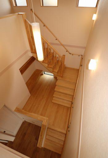 大きな吹き抜けに設けた無垢材のスキップ階段。 自然な木目に、階上の窓からさしこむ柔らかな光があいまって特別な空間に。