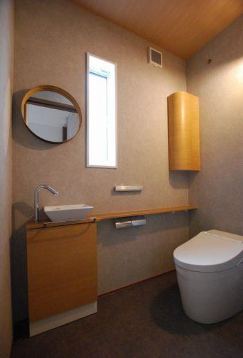 グレートーンでまとめられたトイレは、収納と天井の色をあわせて色数をおさえたことでよりシックな印象に。