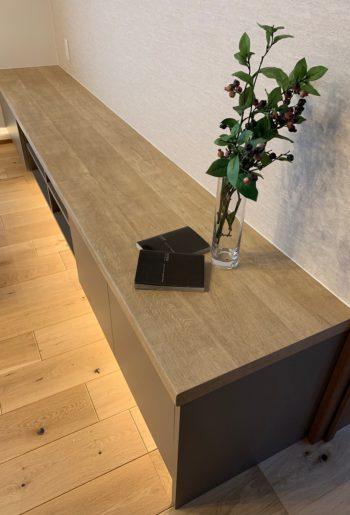 リビングボード下の間接照明は、キッチンの折下げ天井からの照明と、フロアの優しい色あいと相互して、リビングを趣のある空間にする。