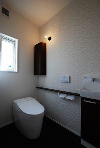シンプルかつこだわりが光るトイレ。電球型のブラケットライトがフォーカルポイントに。
