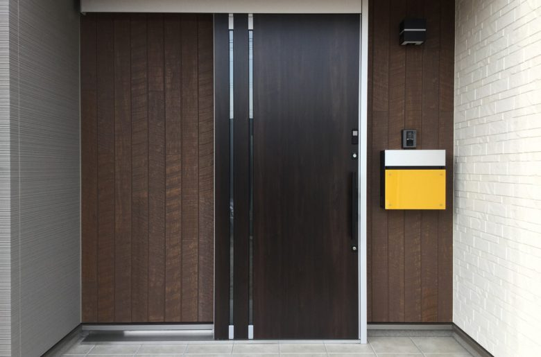 玄関の奥まった箇所はバルコニーの手摺と風合いを揃えて木質感をプラス。ビタミンカラーの黄色いポストが映える、活気ある玄関に!