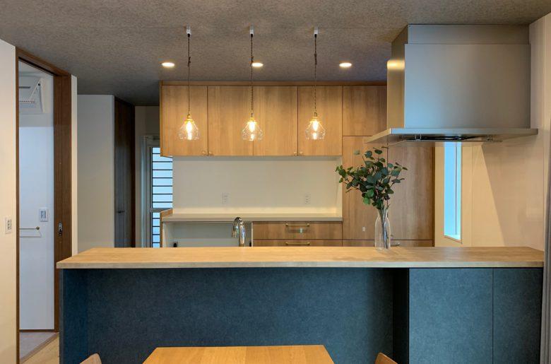 グレートーンの折下げ天井に木目調のキッチンのコントラストが、ペンダントライトのクリアな光で優しいたたずまいに。