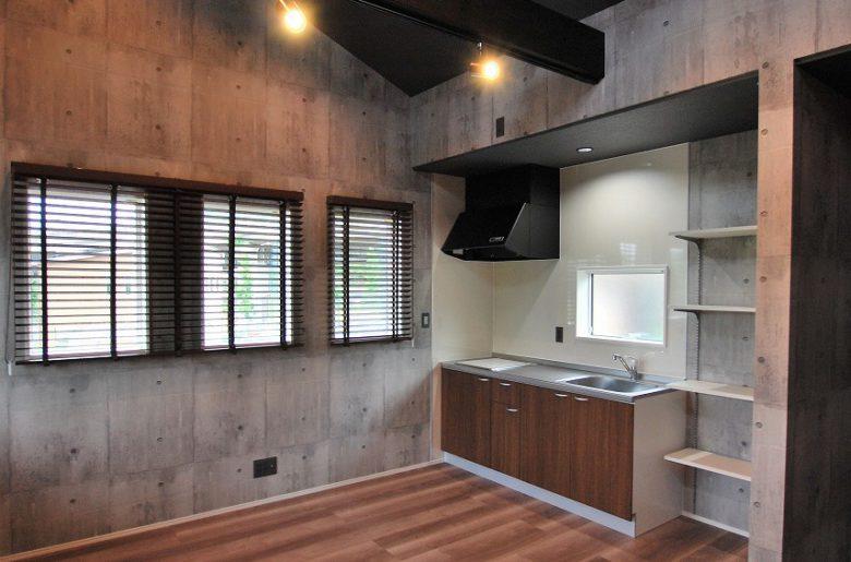 システムキッチンや住宅設備を備えて独立させた部屋は、無機質なコンクリート柄のクロスと木を組み合わせたインダストリアルスタイル。